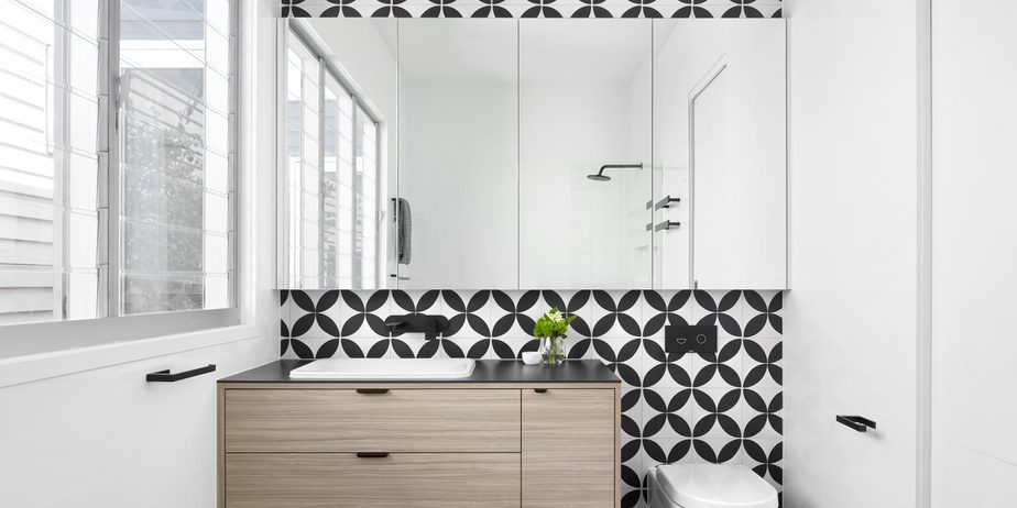 Smarter Bathrooms and Kitchens - a modern bathroom design with combination of black and white geometric bathroom wall tiles and ivory white sink on wooden bathroom vanity. Beautiful bathroom designs built by bathroom renovations Melbourne specialist