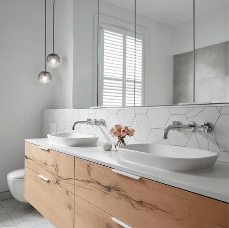 Smarter Bathrooms and Kitchens - an elegant shower, ivory white sink, and beautiful herringbone pattern bathroom wall tiles in a modern bathroom. Beautiful bathroom designs built by bathroom renovations Melbourne specialist